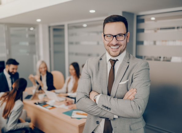 Handsome smiling businessman in formal wear and eyeglasses standing at boardroom with arms crossed.